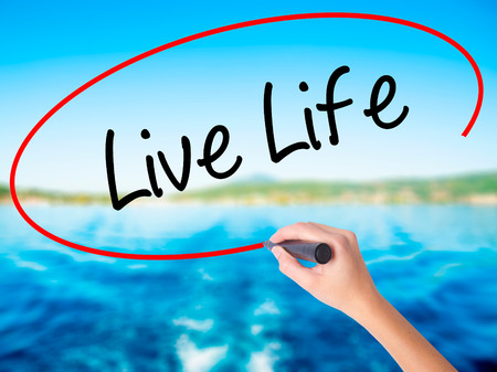 Woman Hand Writing Live Life on blank transparent board with a marker isolated over water background. Business concept. Stock Photo