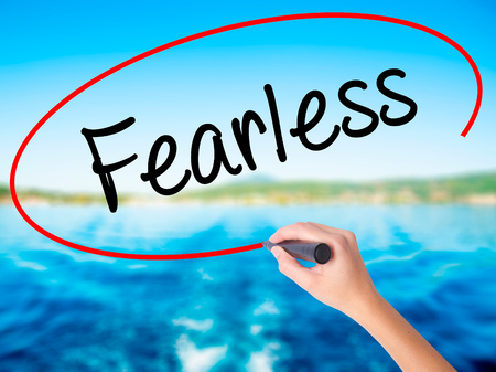 fearless: Woman Hand Writing Fearless  on blank transparent board with a marker isolated over water background. Business concept. Stock Photo