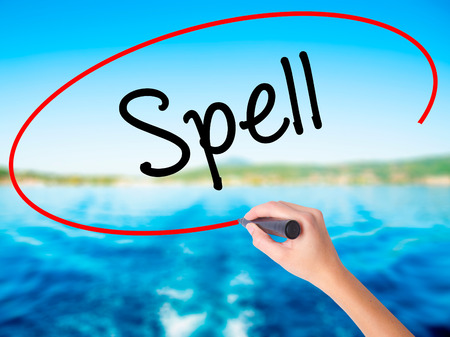 Woman Hand Writing Spell on blank transparent board with a marker isolated over water background. Business concept. Stock Photo