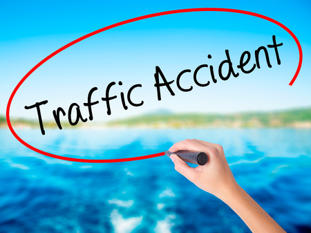 Woman Hand Writing Traffic Accident on blank transparent board with a marker isolated over water background. Business concept. Stock Photo Stock Photo