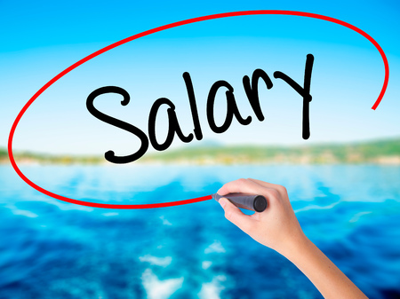 remuneración: Woman Hand Writing Salary  on blank transparent board with a marker isolated over water background. Business concept. Stock Photo