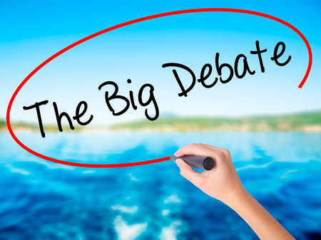 controversy: Woman Hand Writing The Big Debate on blank transparent board with a marker isolated over water background. Business concept. Stock Photo Stock Photo