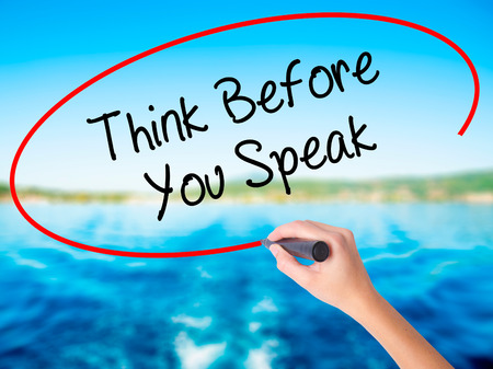 Woman Hand Writing Think Before You Speak on blank transparent board with a marker isolated over water background. Business concept. Stock Photo
