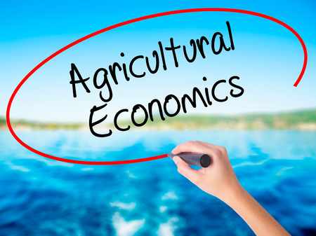 Woman Hand Writing Agricultural Economics on blank transparent board with a marker isolated over water background. Business concept. Stock Photo