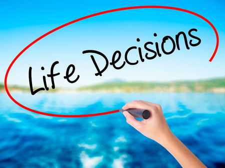 Woman Hand Writing Life Decisions on blank transparent board with a marker isolated over water background. Business concept. Stock Photo