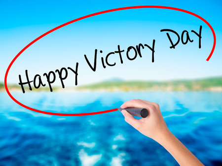 Woman Hand Writing Happy Victory Day with a marker over transparent board. Isolated on background. Business, technology, internet concept. Stock  Photo