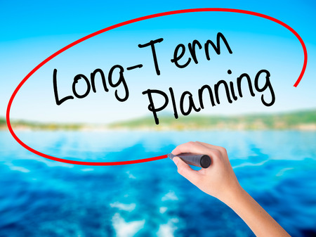 Woman Hand Writing  Long-Term Planning on blank transparent board with a marker isolated over water background. Business concept. Stock Photo Stock Photo