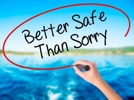 Woman Hand Writing Better Safe Than Sorry on blank transparent board with a marker isolated over water background. Business concept. Stock Photo