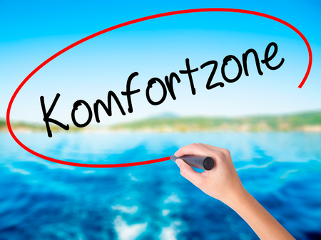 Woman Hand Writing Komfortzone  (Comfort Zone in German)  on blank transparent board with a marker isolated over water background. Business concept. Stock Photo