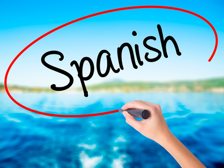 Woman Hand Writing Spanish on blank transparent board with a marker isolated over water background. Business concept. Stock Photo Stock Photo