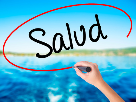 Woman Hand Writing Salud (Health in Spanish) on blank transparent board with a marker isolated over water background. Business concept. Stock Photo