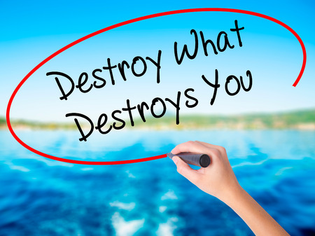 Woman Hand Writing Destroy What Destroys You on blank transparent board with a marker isolated over water background. Business concept. Stock Photo