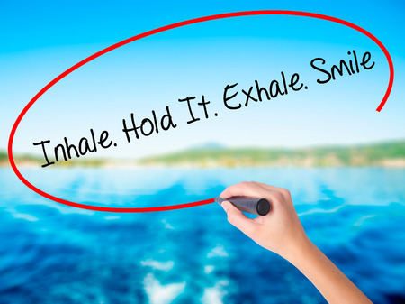 Woman Hand Writing Inhale Hold It Exhale Smile on blank transparent board with a marker isolated over water background. Business concept. Stock Photo