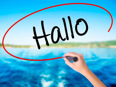 hallo: Woman Hand Writing Hallo  (Hello in German) on blank transparent board with a marker isolated over water background. Business concept. Stock Photo