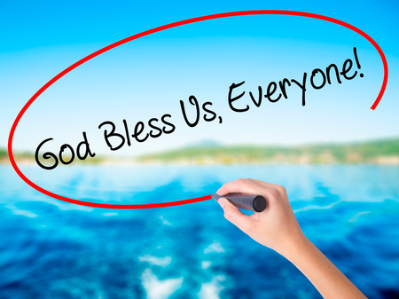 preachment: Woman Hand Writing God Bless Us, Everyone! on blank transparent board with a marker isolated over water background. Business concept. Stock Photo Stock Photo