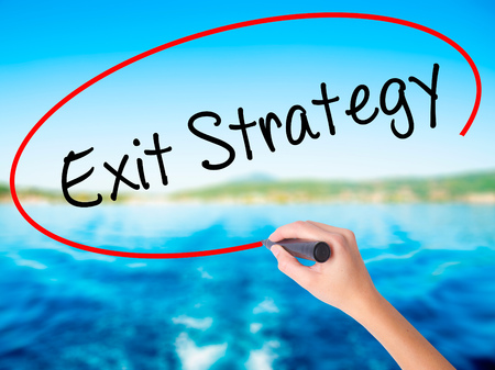 Woman Hand Writing Exit Strategy on blank transparent board with a marker isolated over water background. Business concept. Stock Photo