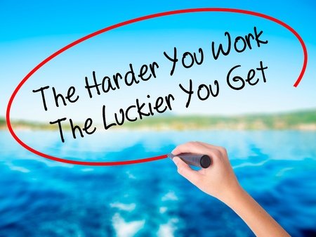 Woman Hand Writing The Harder You Work The Luckier You Get  on blank transparent board with a marker isolated over water background. Business concept. Stock Photo Stock Photo