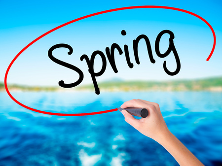 eastertime: Woman Hand Writing Spring on blank transparent board with a marker isolated over water background. Business concept. Stock Photo