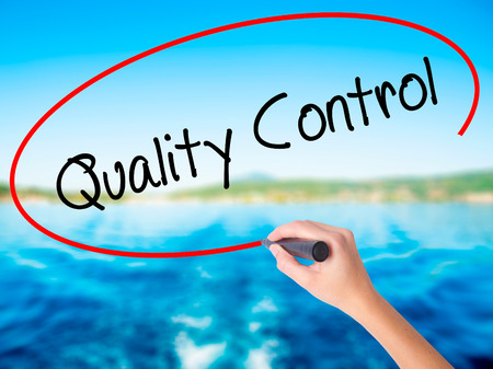 Woman Hand Writing Quality Control on blank transparent board with a marker isolated over water background. Business concept. Stock Photo