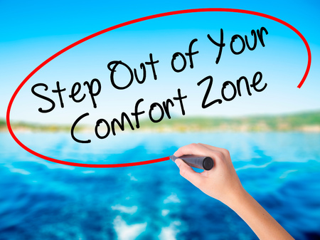Woman Hand Writing Step Out of Your Comfort Zone on blank transparent board with a marker isolated over water background. Business concept. Stock Photo Stock Photo