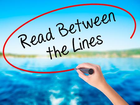 comunicación escrita: Mujer escritura de la mano de leer entre líneas en la tarjeta en blanco transparente con un marcador aislado sobre el fondo del agua. Concepto de negocio. Foto de stock Foto de archivo