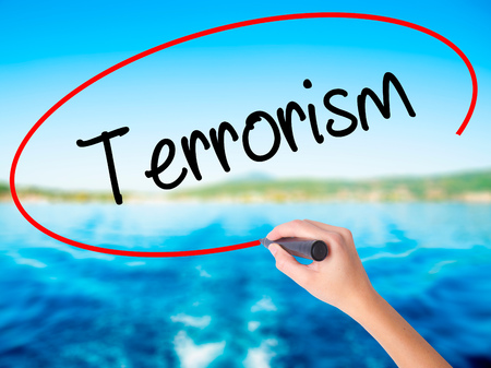 cyber terrorism: Woman Hand Writing Terrorism on blank transparent board with a marker isolated over water background. Business concept. Stock Photo
