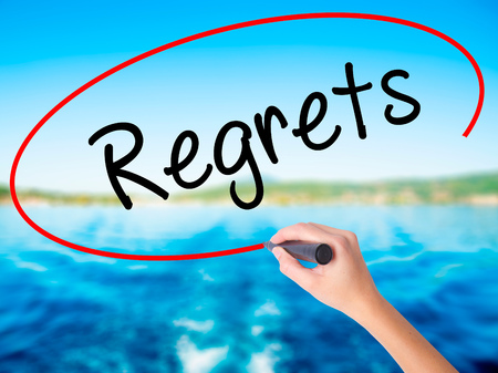 Woman Hand Writing  Regrets on blank transparent board with a marker isolated over water background. Business concept. Stock Photo