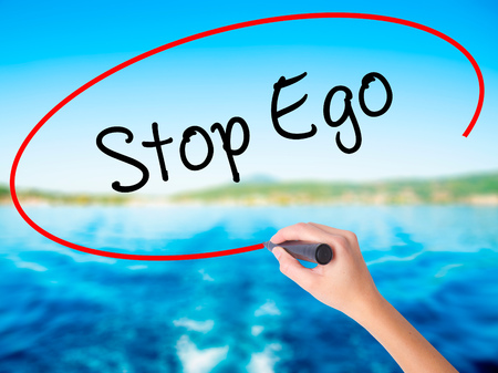 Woman Hand Writing  Stop Ego on blank transparent board with a marker isolated over water background. Business concept. Stock Photo
