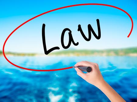 Ley de la escritura de la mano de la mujer en tablero transparente en blanco con un marcador aislado sobre fondo de agua. Concepto de negocio. Foto de stock