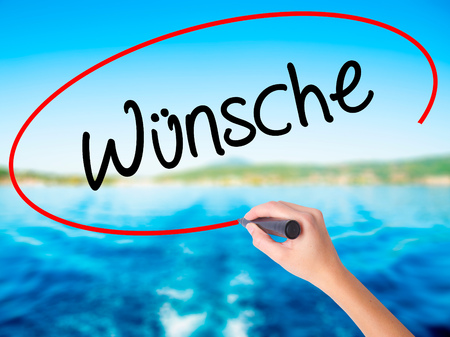 acclaim: Woman Hand Writing Wunsche (Wishes in German) on blank transparent board with a marker isolated over water background. Business concept. Stock Photo Stock Photo