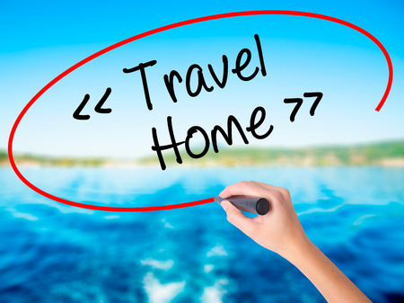Woman Hand Writing Travel - Home on blank transparent board with a marker isolated over water background. Business concept. Stock Photo