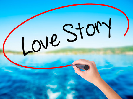 Woman Hand Writing Love Story on blank transparent board with a marker isolated over water background. Business concept. Stock Photo
