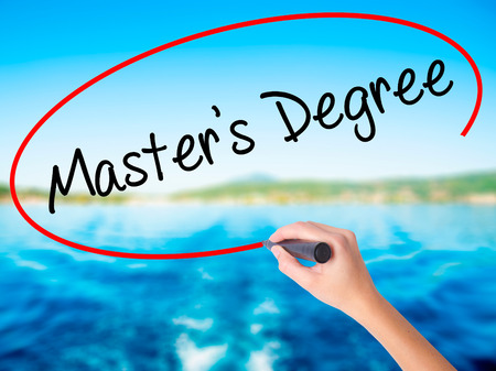 business degree: Woman Hand Writing Masters Degree on blank transparent board with a marker isolated over water background. Business concept. Stock Photo