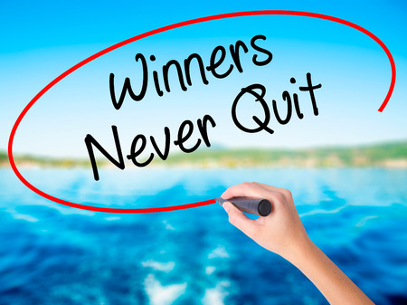 Woman Hand Writing Winners Never Quit on blank transparent board with a marker isolated over water background. Business concept. Stock Photo