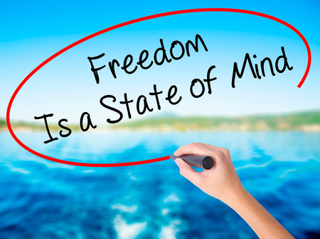 Woman Hand Writing Freedom Is a State of Mind on blank transparent board with a marker isolated over water background. Business concept. Stock Photo