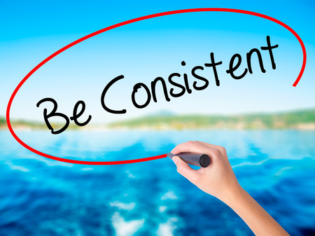 consistency: Woman Hand Writing Be Consistent on blank transparent board with a marker isolated over water background. Business concept. Stock Photo Stock Photo