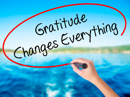 universal love: Woman Hand Writing Gratitude Changes Everything on blank transparent board with a marker isolated over water background. Business concept. Stock Photo