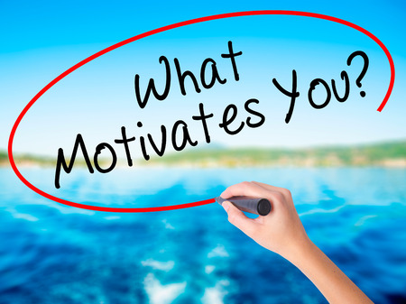 Woman Hand Writing What Motivates You? on blank transparent board with a marker isolated over water background. Business concept. Stock Photo