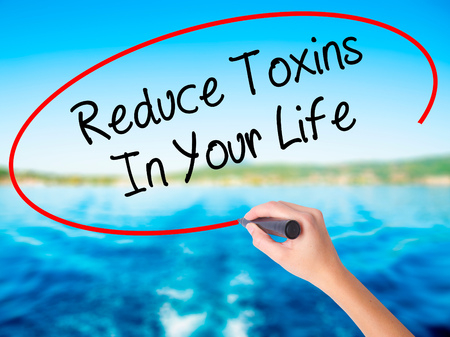 Woman Hand Writing Reduce Toxins In Your Life on blank transparent board with a marker isolated over water background. Business concept. Stock Photo