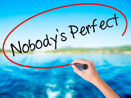 Woman Hand Writing Nobodys Perfect on blank transparent board with a marker isolated over water background. Business concept. Stock Photo