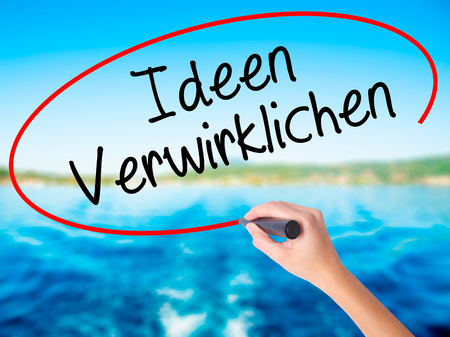 Woman Hand Writing Ideen Verwirklichen ( Realize Ideas in German) on blank transparent board with a marker isolated over water background. Business concept. Stock Photo