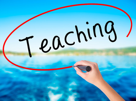 Woman Hand Writing Teaching on blank transparent board with a marker isolated over water background. Business concept. Stock Photo