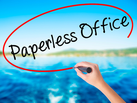paperless: Woman Hand Writing Paperless Office  on blank transparent board with a marker isolated over water background. Business concept. Stock Photo