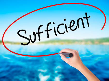 sufficient: Woman Hand Writing Sufficient on blank transparent board with a marker isolated over water background. Business concept. Stock Photo Stock Photo