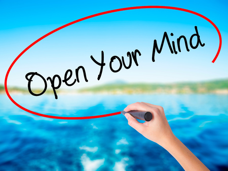 Woman Hand Writing Open Your Mind on blank transparent board with a marker isolated over water background. Business concept. Stock Photo Stock Photo