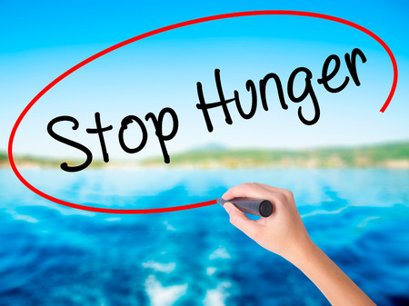 Woman Hand Writing  Stop Hunger on blank transparent board with a marker isolated over water background. Business concept. Stock Photo Stock Photo