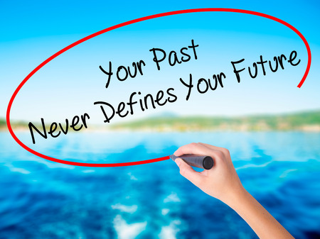 defines: Woman Hand Writing Your Past Never Defines Your Future on blank transparent board with a marker isolated over water background. Business concept. Stock Photo