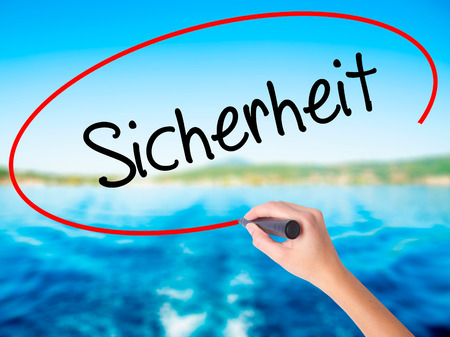 sicherheit: Woman Hand Writing Sicherheit (Safety in German) on blank transparent board with a marker isolated over green field background. Business concept. Stock Photo Stock Photo