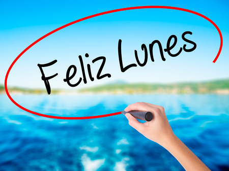 feliz: Woman Hand Writing Feliz Lunes (Happy Monday In Spanish) on blank transparent board with a marker isolated over water background. Business concept. Stock Photo