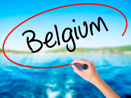 Woman Hand Writing Belgium  on blank transparent board with a marker isolated over water background. Business concept. Stock Photo Stock Photo